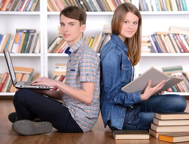 Giovane libro di lettura dello studente e computer portatile usando nella biblioteca
