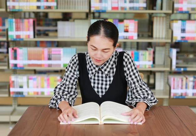 Giovane libro di lettura donna asiatica nella libreria