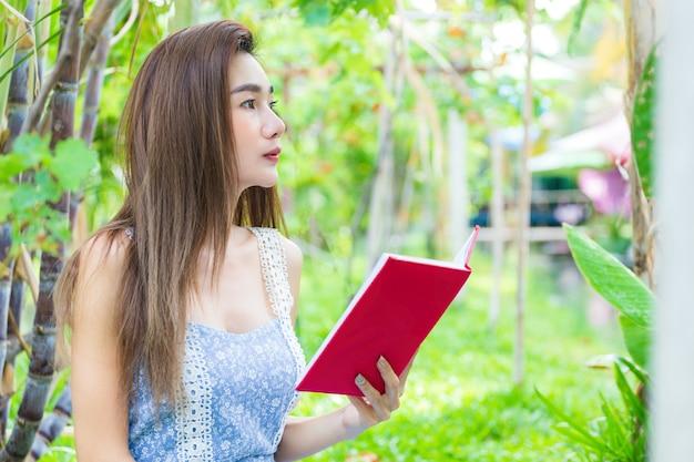 Giovane libro di lettura grazioso della donna in parco