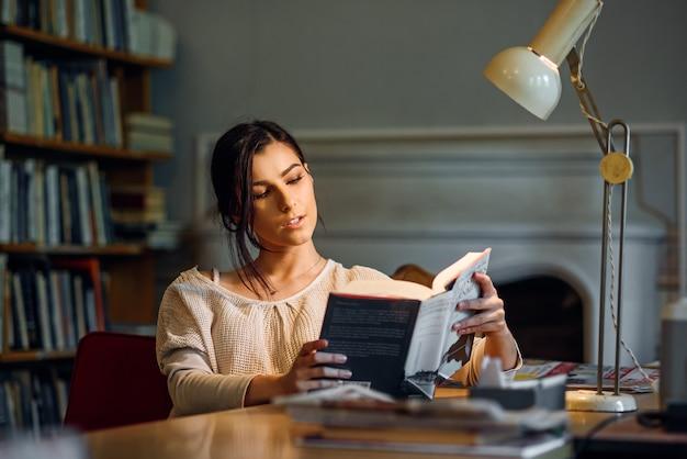 Giovane libro di lettura grazioso ed entusiasta della ragazza dello studente in biblioteca universitaria sotto una lampada da tavolo