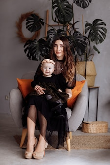 Giovane madre abbastanza alla moda con la piccola figlia sveglia in vestiti scuri che abbracciano e che si siedono sulla sedia a casa, famiglia sorridente felice, concetto della gente di stile di vita. la mamma, il giorno del bambino