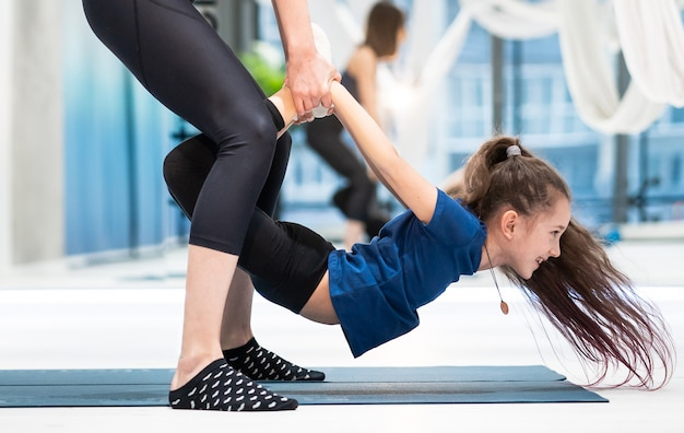 Giovane madre adulta che aiuta sua figlia a fare l'esercizio