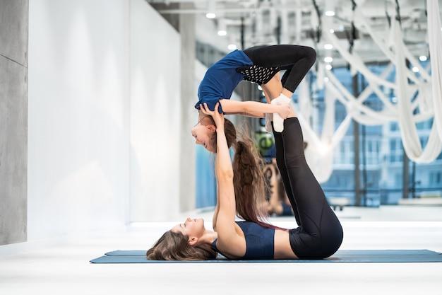 Giovane madre adulta che fa forma fisica con la sua piccola figlia