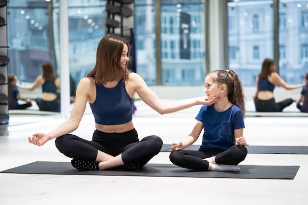 Giovane madre adulta e piccola figlia che praticano insieme yoga