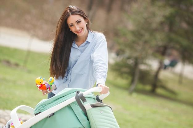 Giovane madre allegra che cammina con il suo bambino in carriege