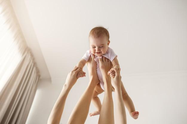 Giovane madre allegra che gioca con il suo bambino appena nato che si trova sul letto a casa.