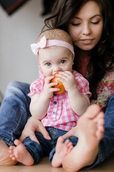 Giovane madre amorosa che ride abbracciando la figlia divertente sveglia sorridente del bambino che gode insieme del tempo a casa