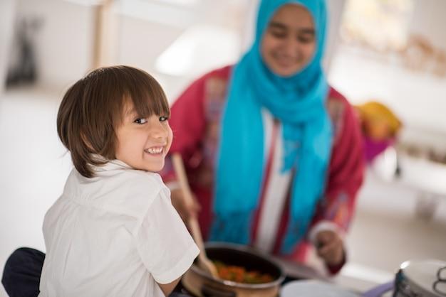 Giovane madre araba musulmana e piccolo figlio sveglio che producono alimento e che si divertono nella cucina