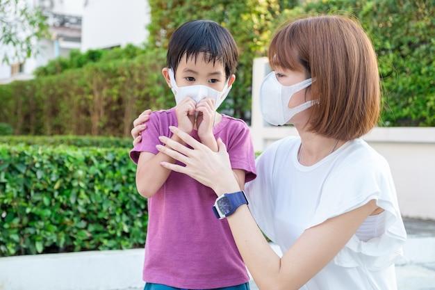 Giovane madre asiatica che indossa la maschera protettiva pm2.5 per suo figlio al parco all'aperto