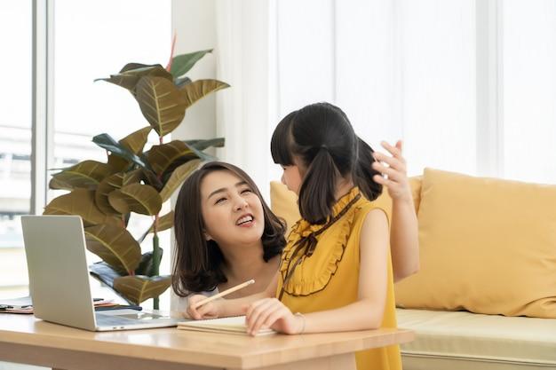 Giovane madre asiatica con il computer portatile che insegna al bambino a imparare o studiare in linea a casa, concetto in linea di homeschooling