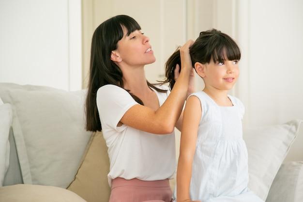 Giovane madre caucasica che tiene i capelli di sua figlia