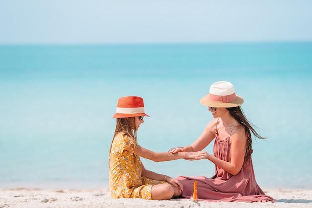 Giovane madre che applica la crema del sole al naso della figlia sulla spiaggia. protezione solare