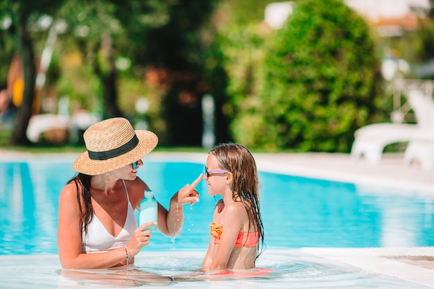 Giovane madre che applica la crema solare al naso della figlia