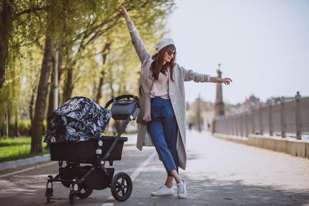Giovane madre che cammina con carrozzina nel parco