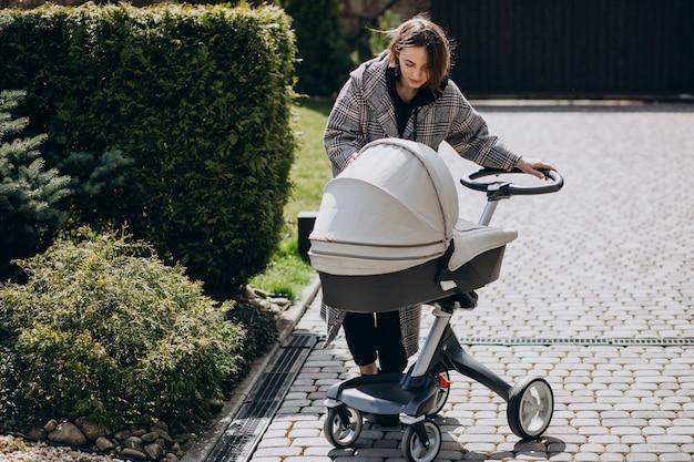 Giovane madre che cammina con la carrozzina in parco