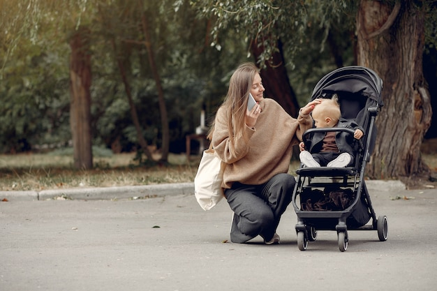 Giovane madre che cammina in un parco di autunno con il trasporto