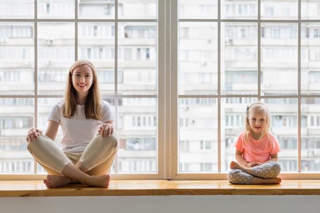 Giovane madre che fa yoga con una figlia di 3 anni davanti alla finestra. mamma felice che sorride mentre praticando yoga insieme alla sua ragazza sveglia che si siede nell'asana di posa del loto