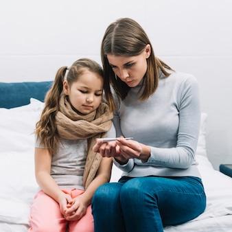 Giovane madre che mostra la temperatura di sua figlia malata sul termometro