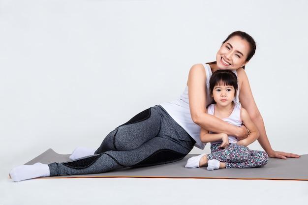 Giovane madre che prepara figlia adorabile con yoga