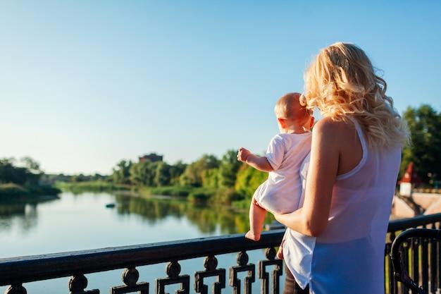 Giovane madre che tiene bambino e che mostra il paesaggio del fiume.