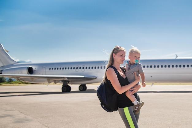 Giovane madre che tiene suo figlio del bambino sull'aeroplano e sul cielo blu all'aeroporto