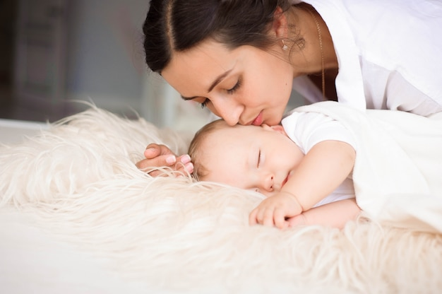 Giovane madre che tiene teneramente il suo bambino appena nato