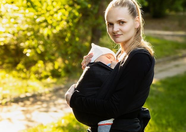 Giovane madre che trasporta un neonato sleepimg bambino.
