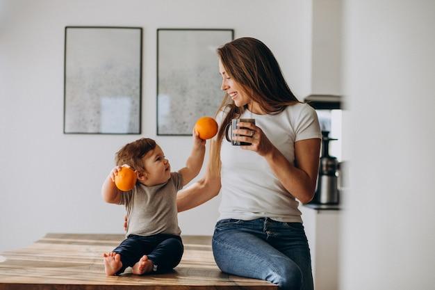 Giovane madre con acqua potabile del piccolo figlio a casa