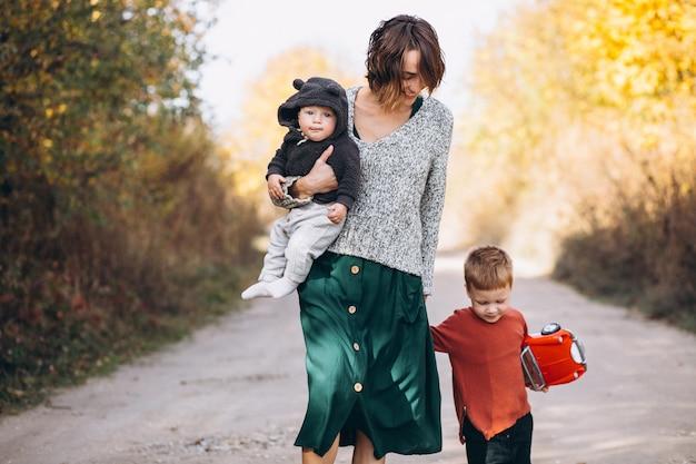 Giovane madre con due figli che camminano nel parco