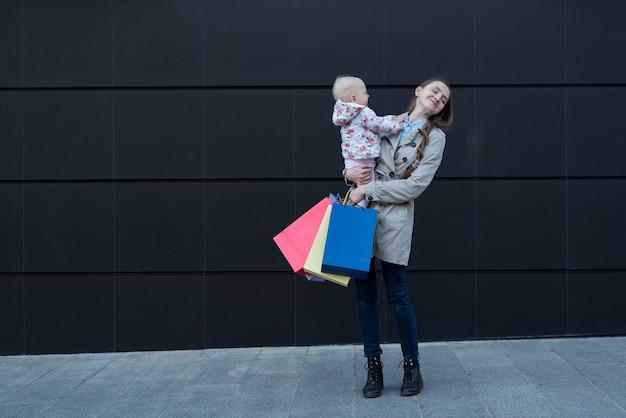 Giovane madre con figlia piccola sulle braccia e borse della spesa in mano.
