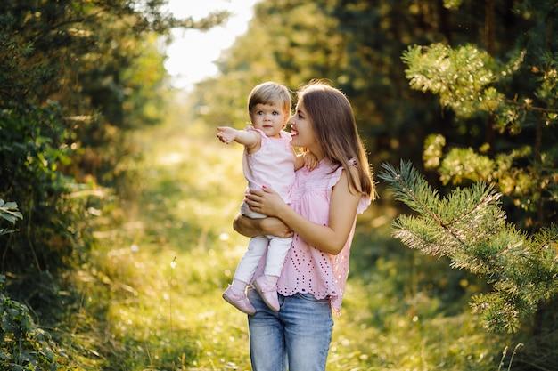 Giovane madre con il suo adorabile piccolo bambino nella foresta