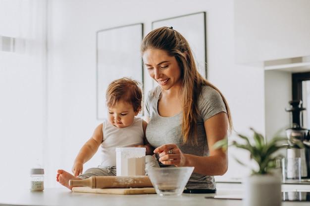 Giovane madre con il suo piccolo figlio che cucina alla cucina