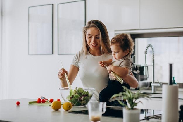 Giovane madre con il suo piccolo figlio che produce insalata alla cucina