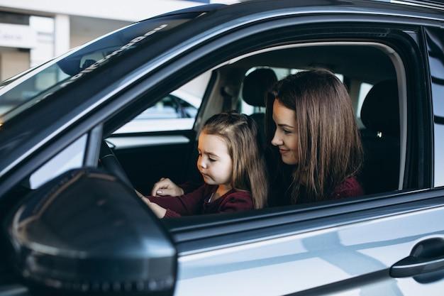 Giovane madre con la piccola figlia che si siede dentro un'automobile