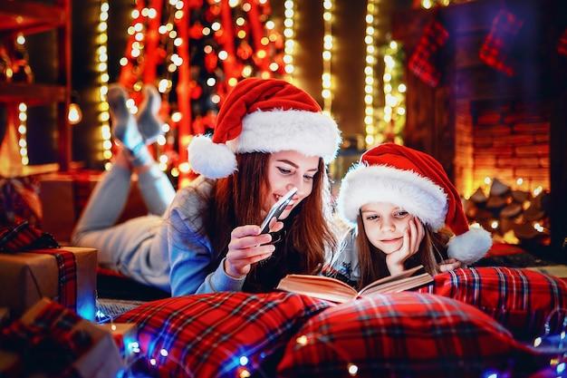 Giovane madre con la sua piccola figlia che legge un libro mentre sedendosi sotto l'albero di natale decorato sul pavimento