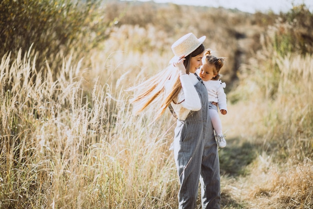 Giovane madre con la sua piccola figlia in un campo di autunno