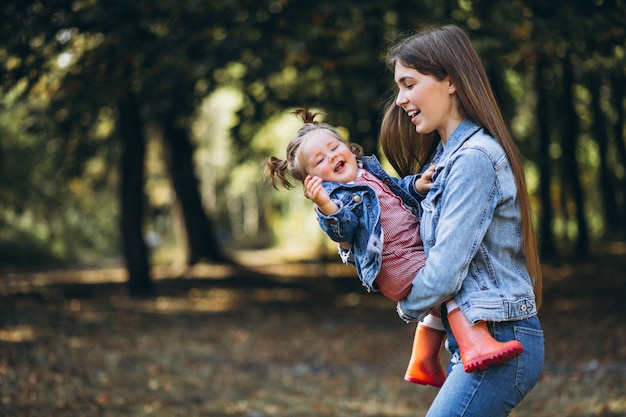 Giovane madre con la sua piccola figlia in un parco di autunno