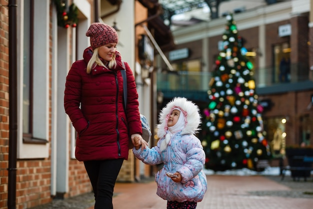 Giovane madre con sua figlia shopping sul mercato esterno di natale