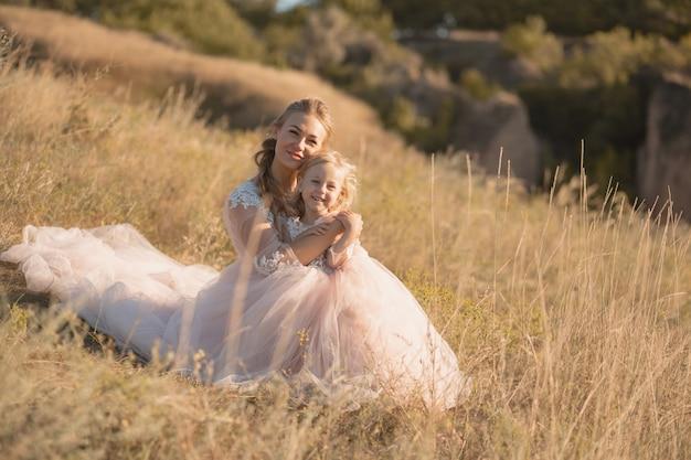 Giovane madre con una figlia piccola in abiti rosa sono seduti sul campo, la mamma abbraccia la figlia, abbracciandola