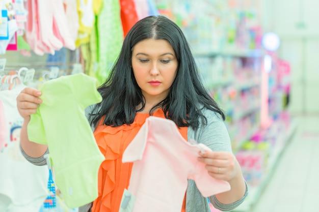 Giovane madre della donna del brunette che osserva e che sceglie le camice dei bambini al negozio di vestiti