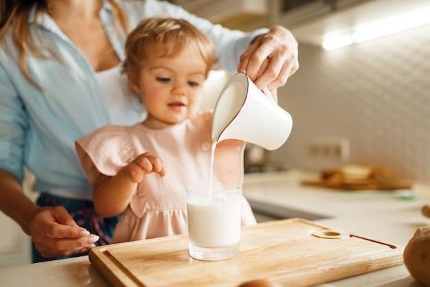 Giovane madre e bambino versa il latte in un bicchiere, ingredienti per pasticceria