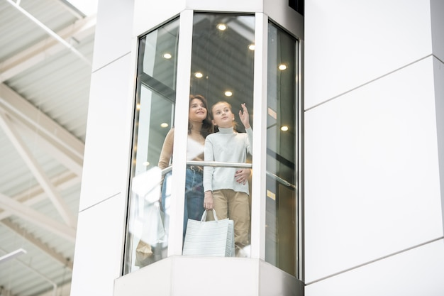 Giovane madre e figlia che parlano di qualcosa mentre si muove verso l'alto in ascensore durante lo shopping del venerdì nero nel centro commerciale