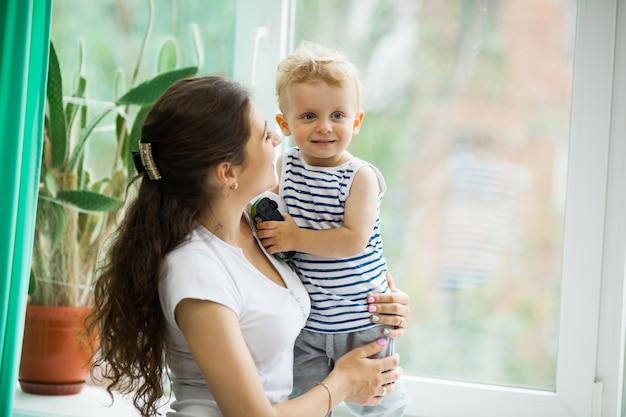 Giovane madre e figlio a guardare la pioggia attraverso la finestra