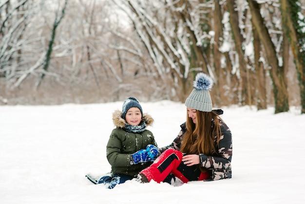 Giovane madre e figlio divertirsi nel parco d'inverno