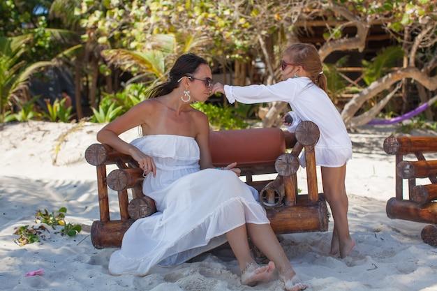 Giovane madre e le sue piccole figlie che odorano i fiori sulla spiaggia tropicale