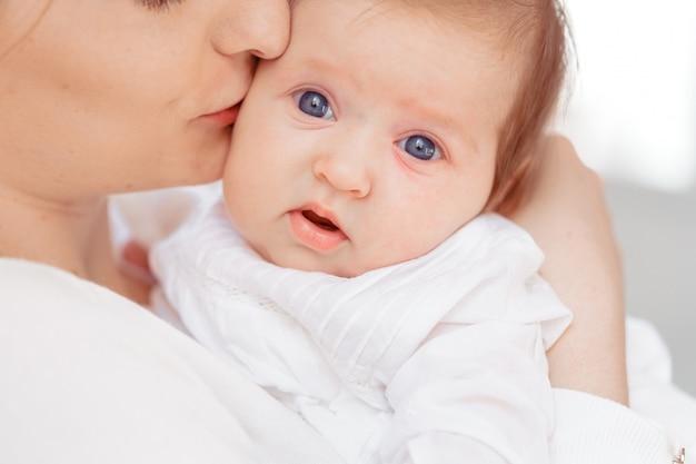 Giovane madre e neonato in camera da letto bianca