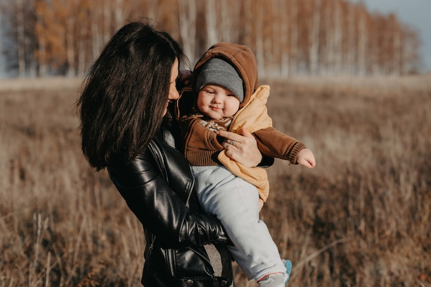 Giovane madre felice allegra con suo figlio del ragazzo del neonato in sue mani in autunno