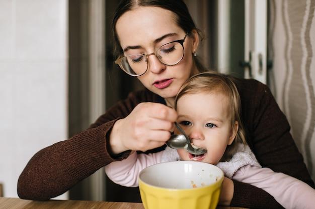 Giovane madre felice che alimenta il suo piccolo bambino con minestra saporita deliziosa dal piatto alla cucina.