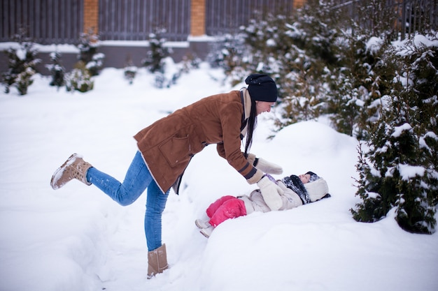 Giovane madre felice con la sua piccola figlia sveglia divertendosi nel cortile un giorno di inverno