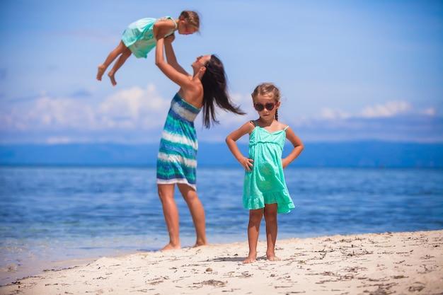 Giovane madre felice e le sue adorabili figlie divertirsi in spiaggia esotica in giornata di sole